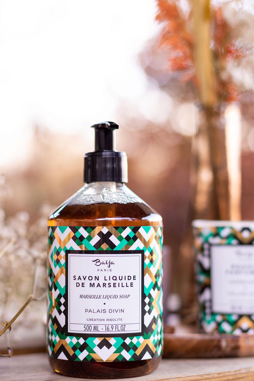 Le flacon pompe du savon de Marseille liquide de Baïja posé sur une table en bois devant un bouquet de fleurs séchées pour le top 3 des gels douche