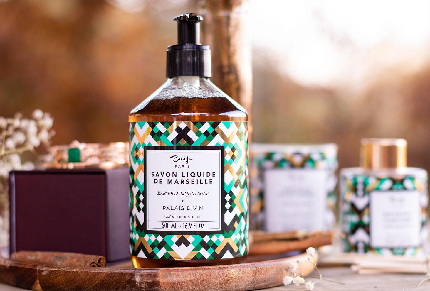 Le savon liquide de Marseille de la gamme Palais Divin de Baïja posé sur une planche en bois au milieu de bijoux et de fleurs séchées blanches