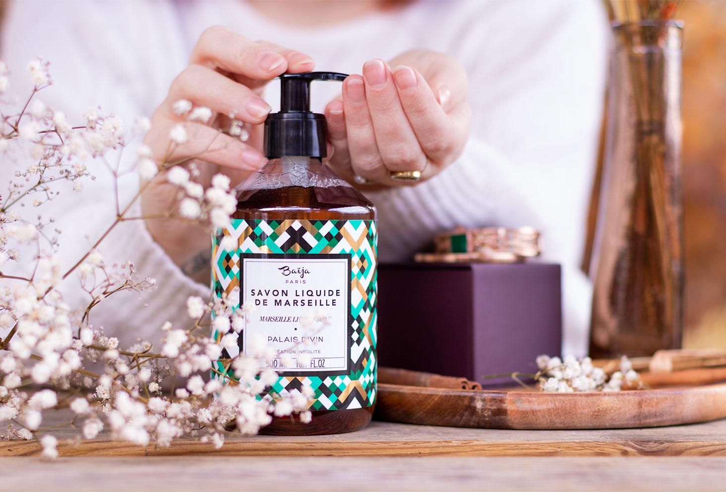 Utilisation de la pompe au creux de la main, du savon liquide de Marseille de Baïja, posé au milieu de fleurs sèches et de bijoux sur une table en bois pour le top 3 des gels douche