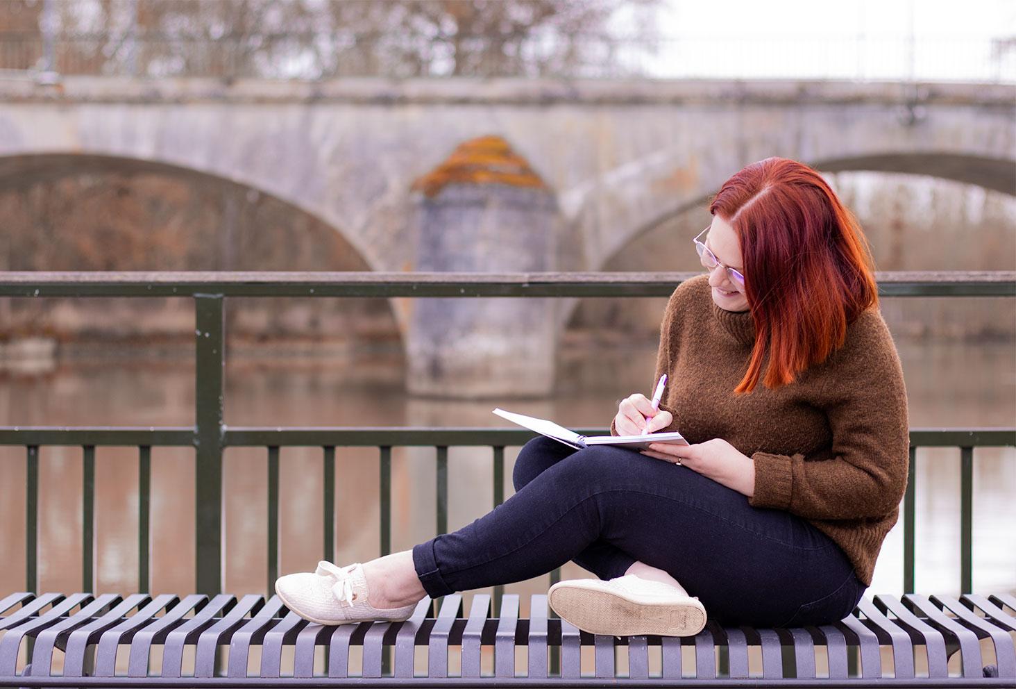 Assise sur un banc devant la rivière, en train d'écrire avec envie dans un carnet, en jean noir et pull à col roulé marron