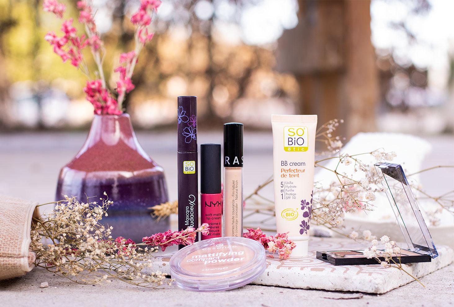 Trousse à maquillage avec des produits à petits prix, moins de 50€ posé sur une dalle en béton au milieu de fleurs séchées
