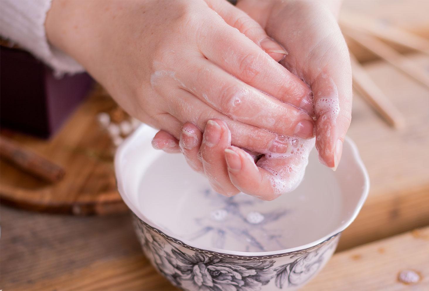 Mousse sur les mains à l'utilisation du savon liquide de Marseille de la gamme Palais Divin de Baïja, au-dessus d'un bol rempli d'eau