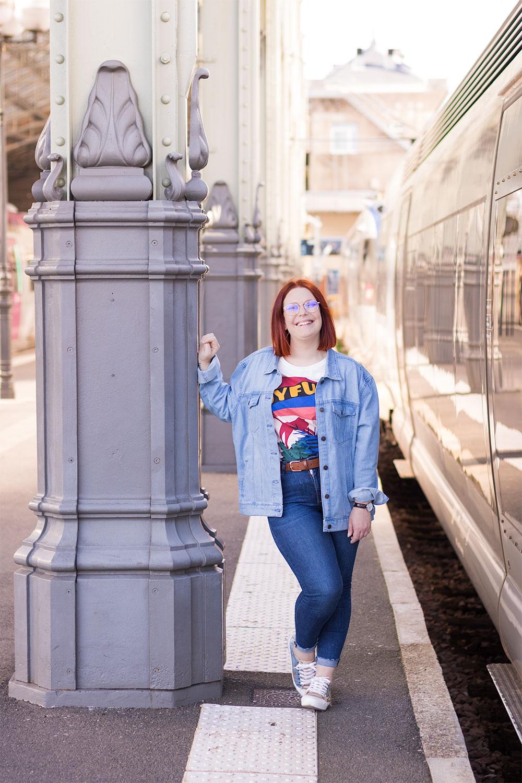 Appuyée contre un poteau à la gare de Tours, en jeans baskets et veste loose, à côté d'un train