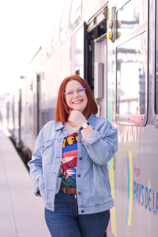 Devant la porte ouverte du train, en veste en jean loose avec le sourire