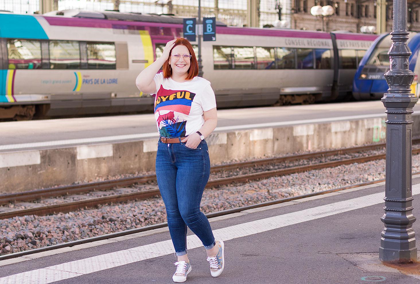 En jean bleu et t-shirt Joyful loose, sur le quai de la gare, une main sur la tête de profil