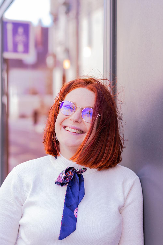 Appuyée de profil contre la vitrine d'un café, avec le sourire et les cheveux dans le vent