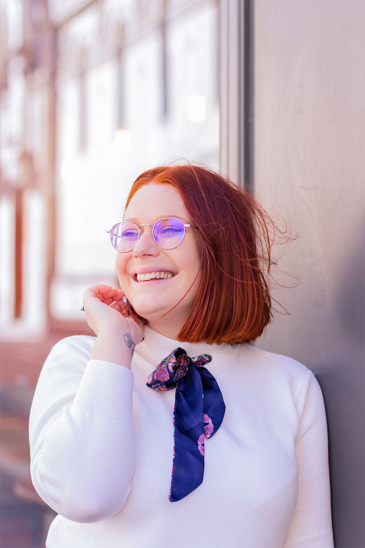 Une main dans le bas des cheveux, appuyée de profil contre la vitrine d'un café, avec le sourire et un foulard noué autour du coup