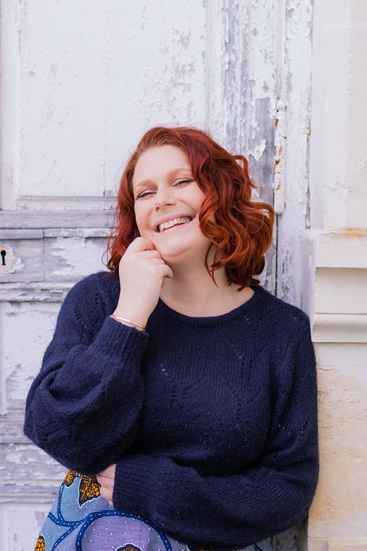 Appuyée contre une porte avec le sourire, en pull bleu marine et cheveux bouclés