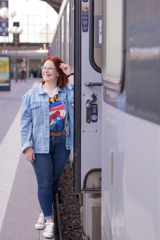 Appuyée le long d'un train de la gare de Tours, avec le sourire et une main dans les cheveux