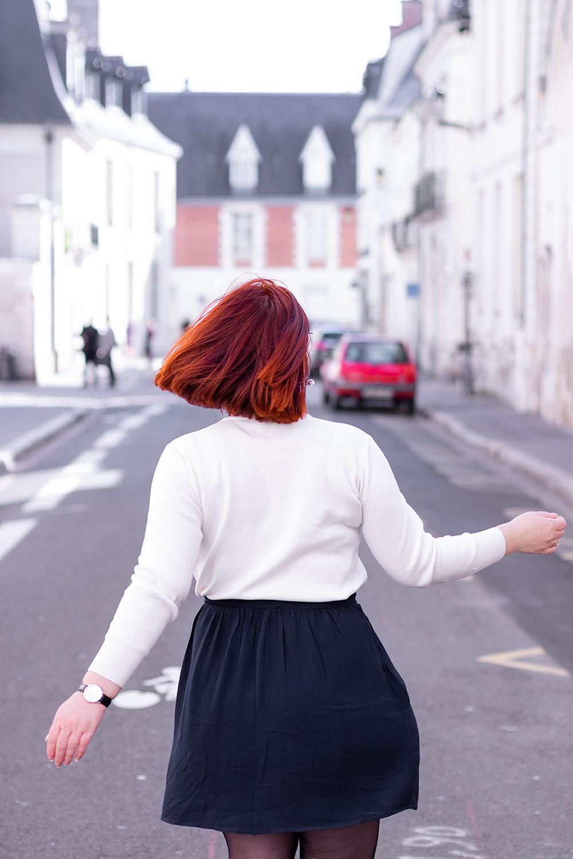 De dos dans la rue, en jupe qui tourne fluide bleue et pull blanc