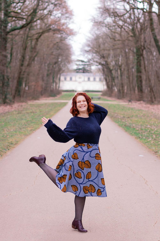 La jambe et le bras en l'air, avec la jupe Aurore bleue de la marque Maison Elpida, dans la grande allée d'un château