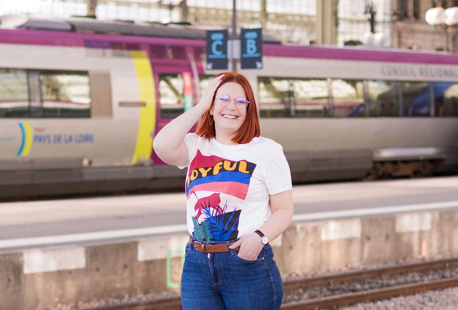 En t-shirt loose Joyful de face, une main dans les cheveux, devant un train coloré