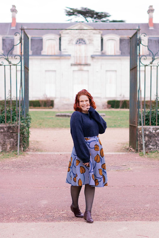 Devant les grilles d'un château, en jupe WAX bleu Maison Elpida