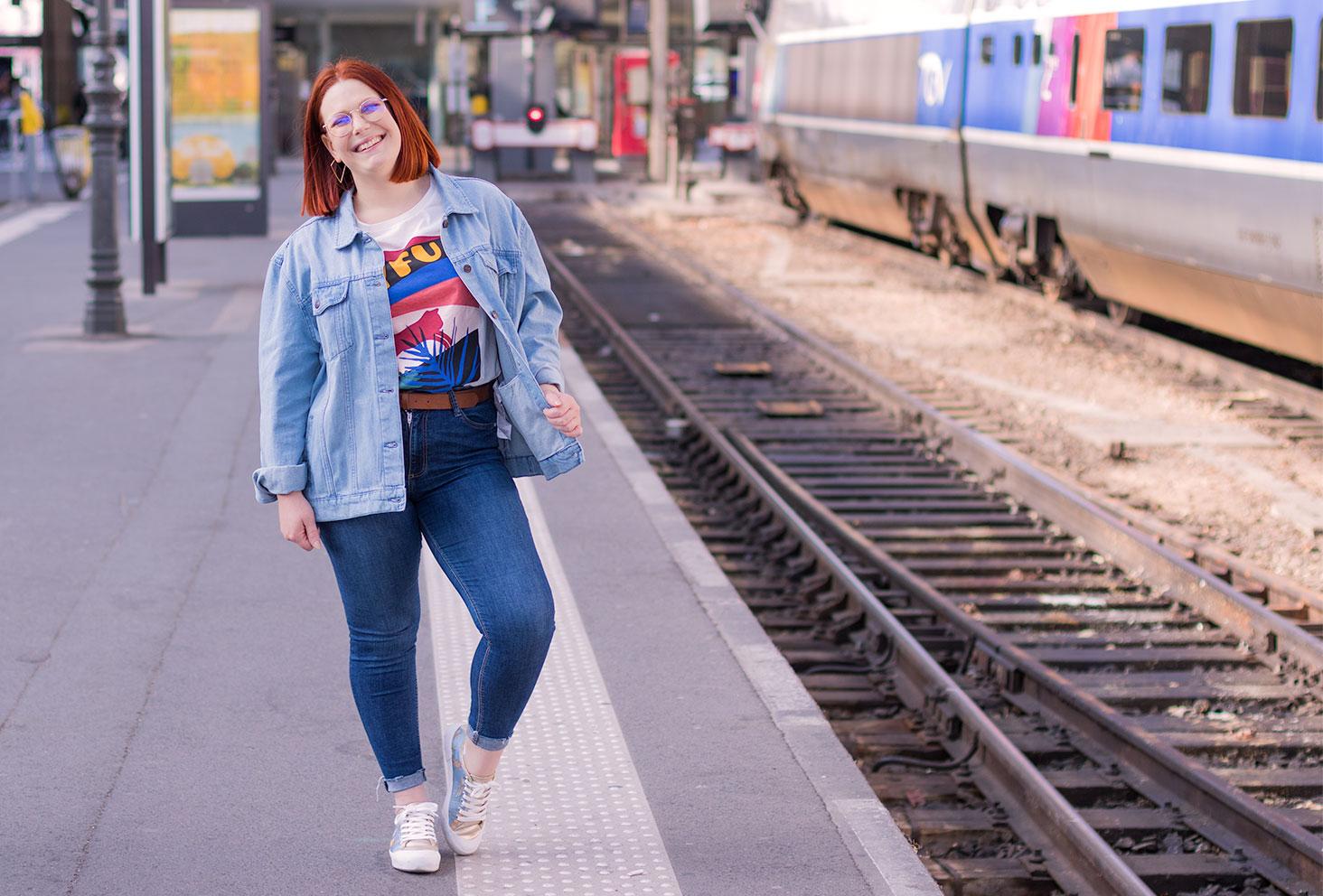 Le long des quais de la gare de Tours, en veste loose en jean avec le sourire