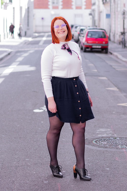 Look du sourire en entier dans la rue, jupe bleue fluide, pull blanc à col cheminée SheIn et bottine noire à talons hauts