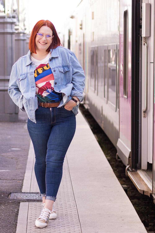 Le long d'un train prêt à partir, les mains dans les poches, en veste en jean loose