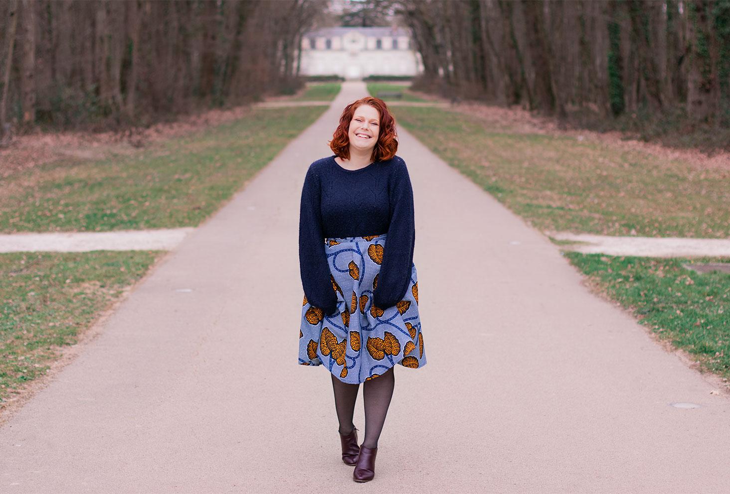 Dans l'allée d'un château, en jupe patineuse Maison Elpida, le sourire et les cheveux bouclés