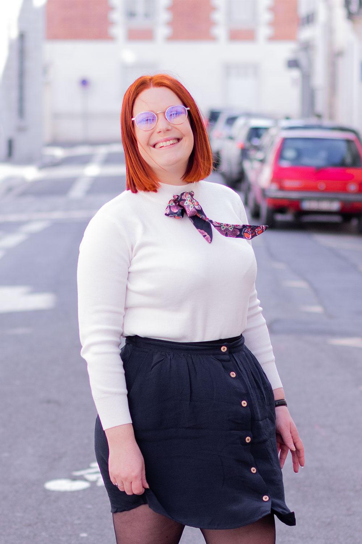 De profil, les cheveux et le foulard dans le vent, avec le sourire dans une rue Toourangelle