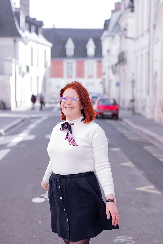 Dans la rue, en train de faire tourner la jupe fluide bleue Kiabi, avec le sourire et les cheveux dans le vent