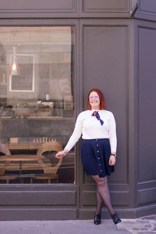 Devant la vitrine d'un café en jupe fluide bleue, pull blanc et bottine à talon haut