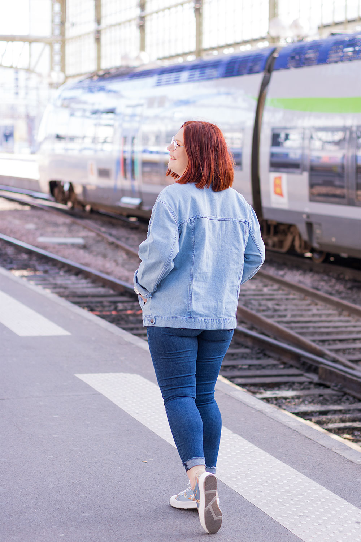 De dos devant le quai de la gare en look en jean