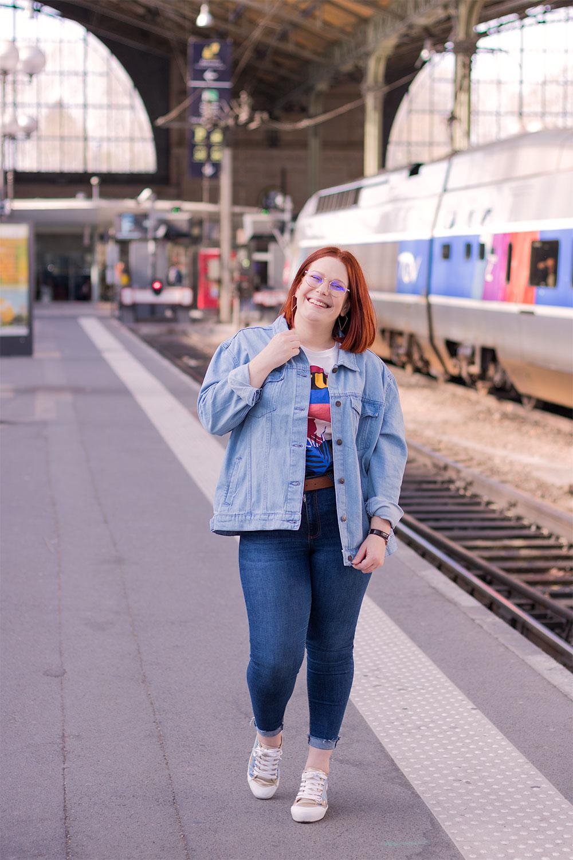 Look en veste loose et jean bleu, le long des quais de la gare, avec le sourie