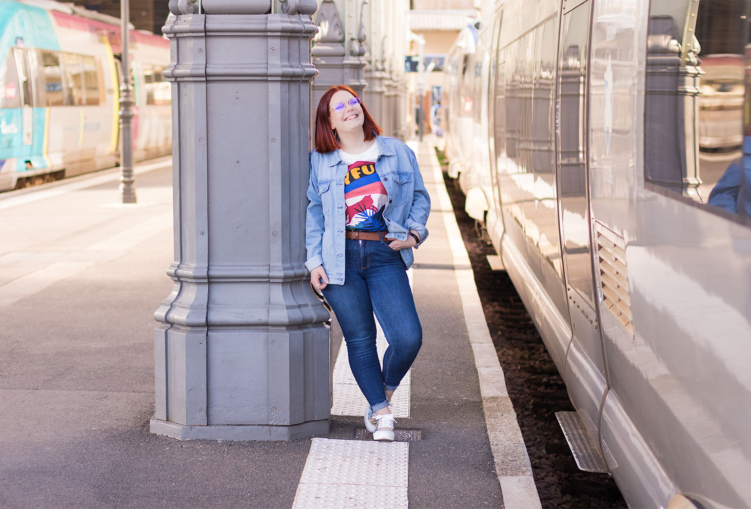 Appuyée le long d'un poteau avec le sourire, en jean et veste loose, le long d'un train