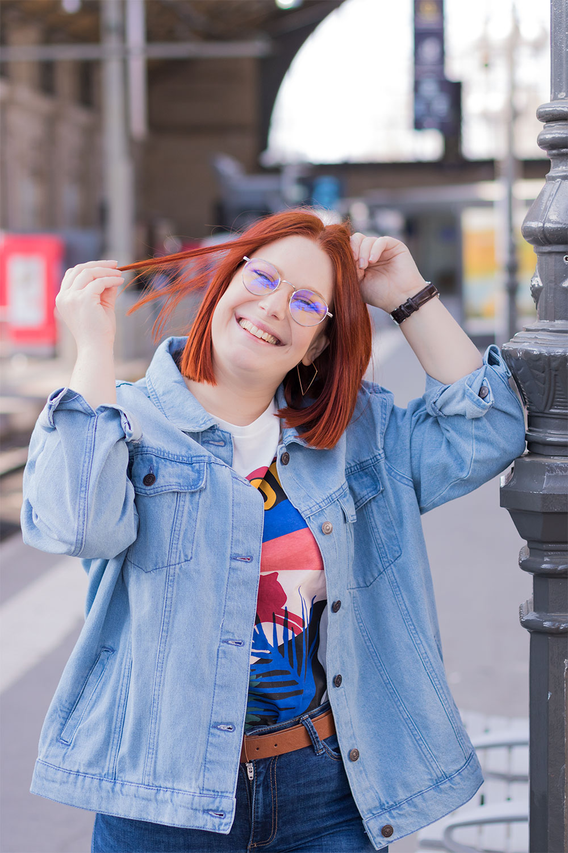 une main dans les cheveux avec le sourire, accoudée à un poteau de la gare de Tours, en veste en jean loose pour un style street