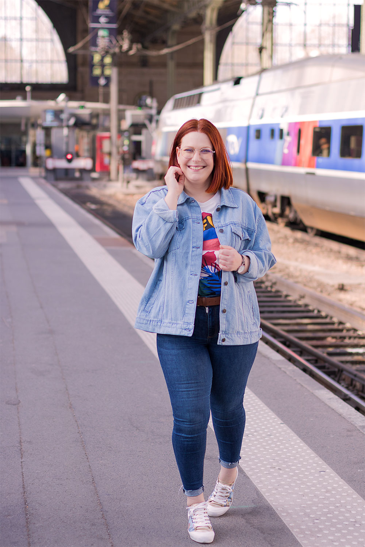 En train de marcher le long des railles de la gare de Tours, en veste en jean et jean bleu marine, avec le sourire