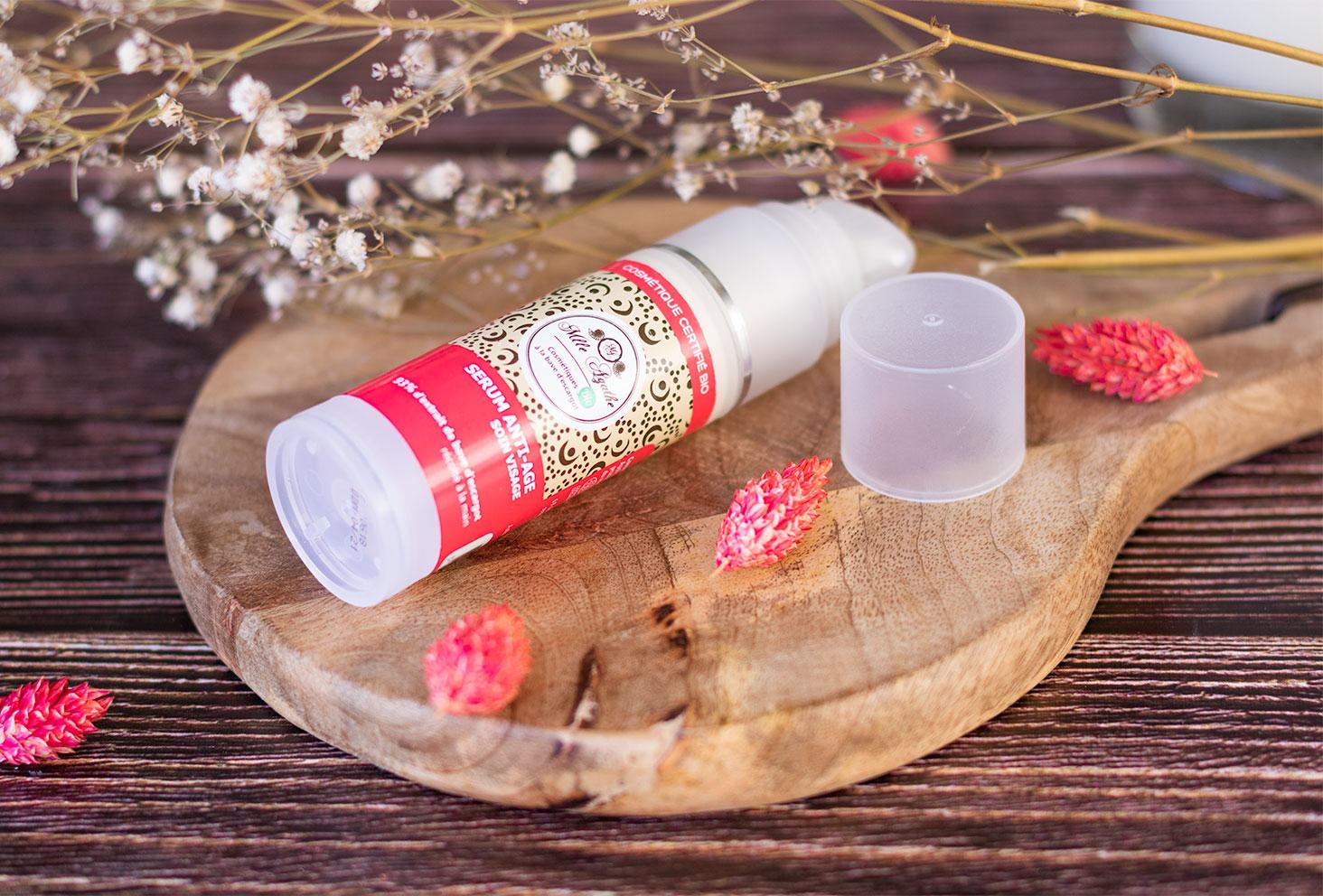 Le sérum anti-âge de Mlle Agathe, couché et ouvert, sur une planche à découper au milieu de fleurs séchées roses et blanches