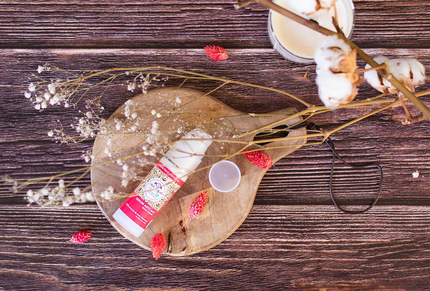 Le sérum de Mlle Agathe sur une planche à découper, sur une table en bois, au milieu de fleurs sèches à côté d'une bougie