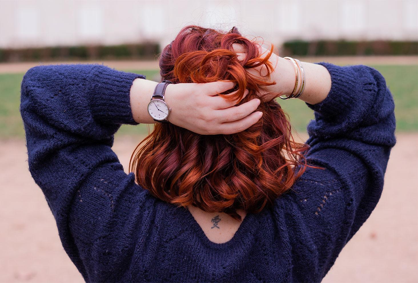 Zoom sur la montre marron Daniel Wellington, les mains dans les cheveux roux bouclés, de dos
