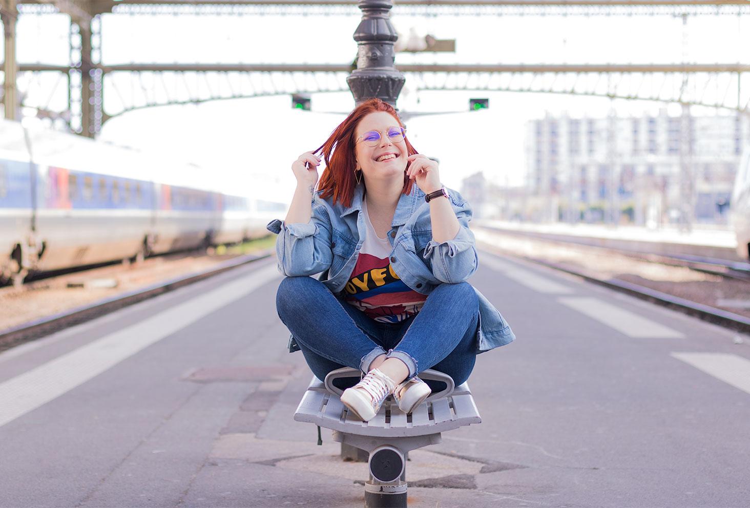 Assise sur un banc, une main dans les cheveux avec le sourire