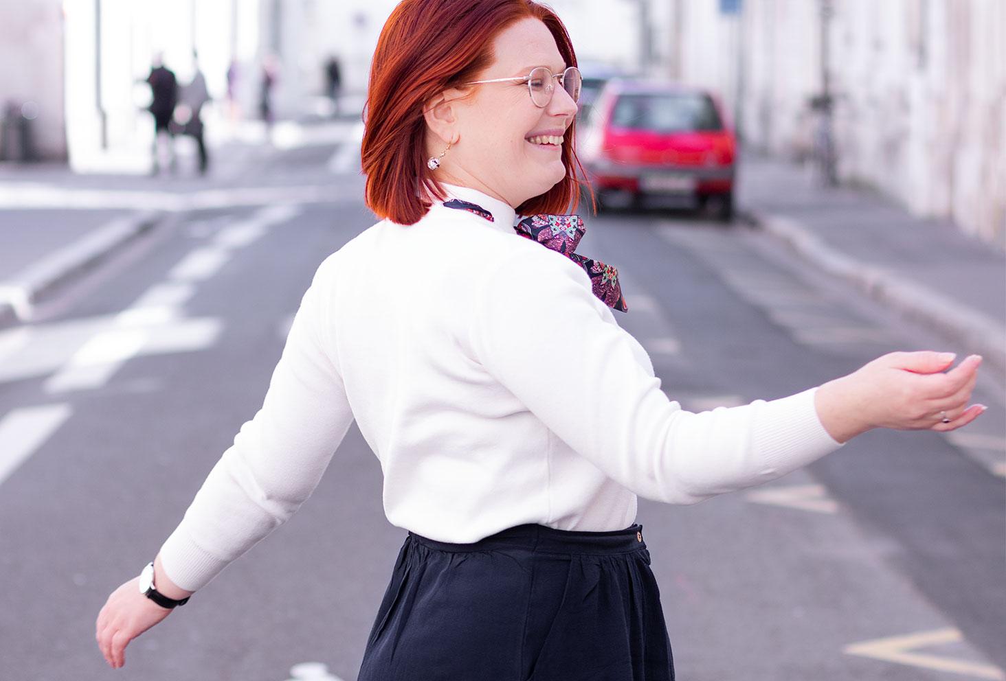 De profil avec le vent dans les cheveux, en train de faire tourner la jupe bleue, en pull blanc SheIn