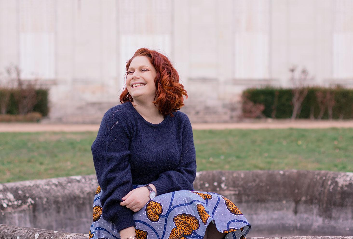 Assise sur le rebord d'une fontaine dans la cours d'un château, regarde de profil avec le sourire, en jupe WAX et pull en laine