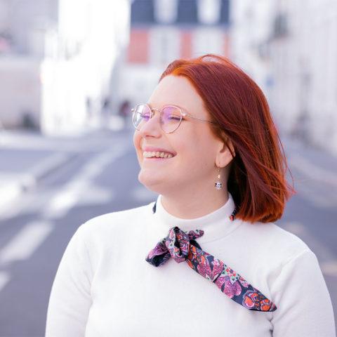 De profil les cheveux dans le vent avec le sourire pour l'article sur le sourire, avec un pull blanc Shein