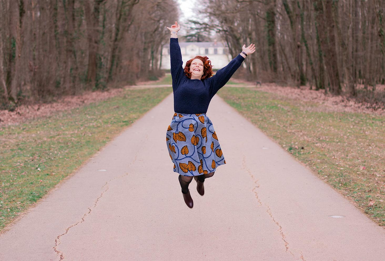 En plein saut, au milieu d'une allée de château, les bras en l'air en pull en laine et jupe en WAX