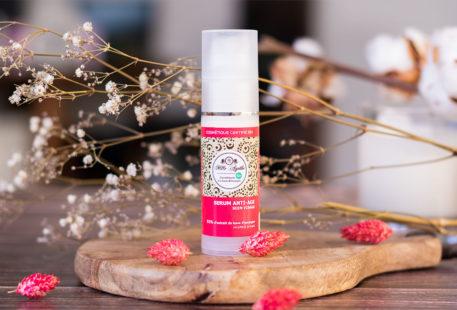 Le sérum anti-âge de Mlle Agathe pour le visage, debout sur une planche à découper en bois devant une bougie au milieu de fleurs séchées roses et blanches