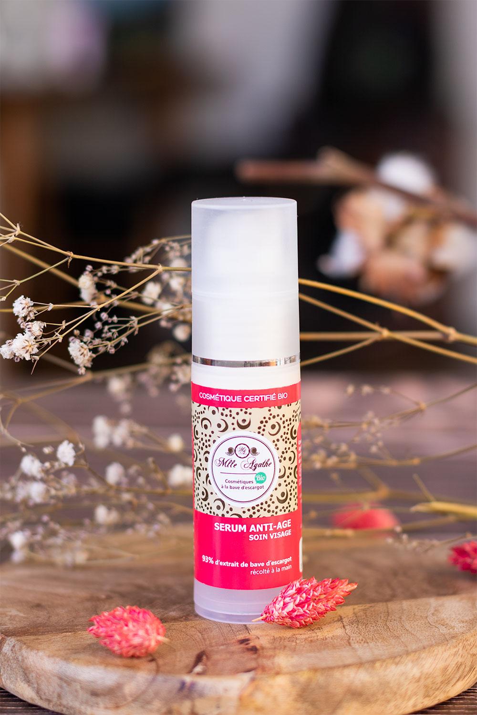 Zoom sur le packaging rose du sérum anti-âge de Mlle Agathe posé sur une table en bois au milieu de fleurs séchées blanches et roses
