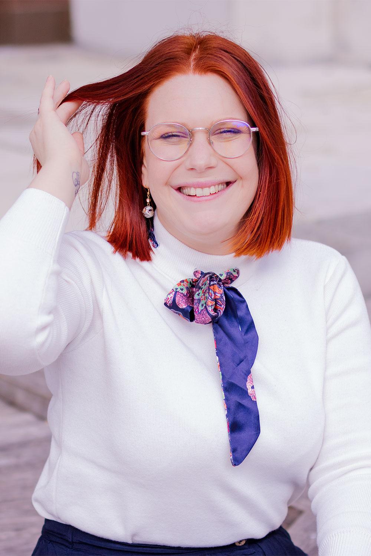 Une main dans les cheveux roux, de face avec le sourire, en pull blanc avec un foulard bleu autour du cou