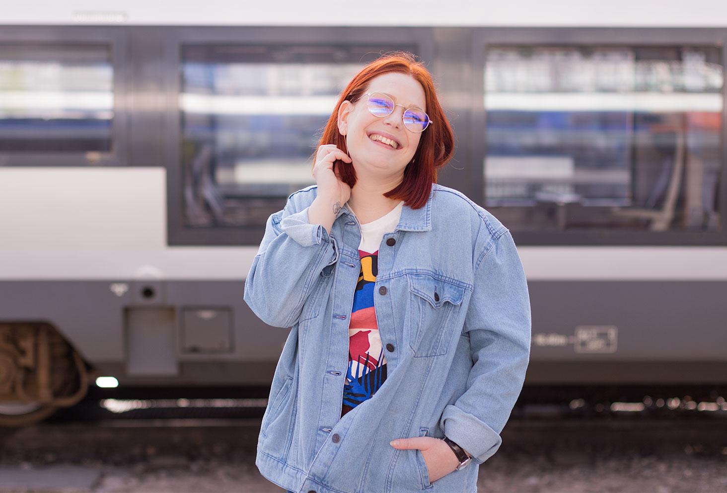 Devant un train, la main dans les cheveux avec le sourire, en veste loose en jean Kiabi