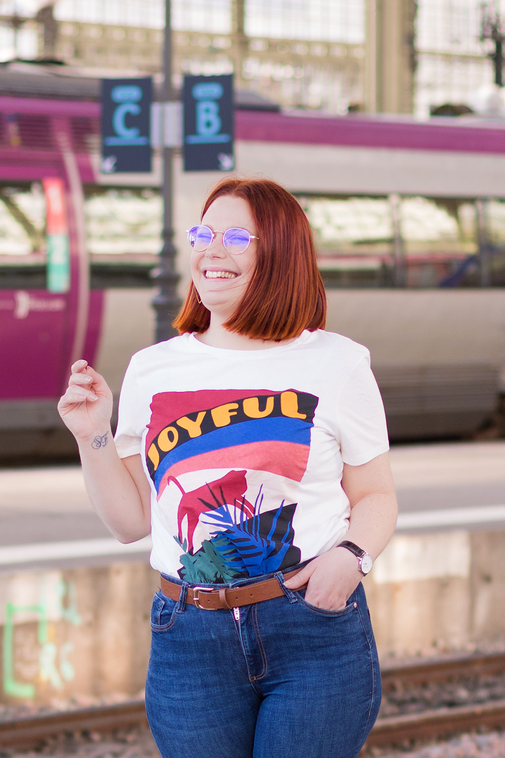 Devant le train rose avec le sourire en t-shirt Joyful