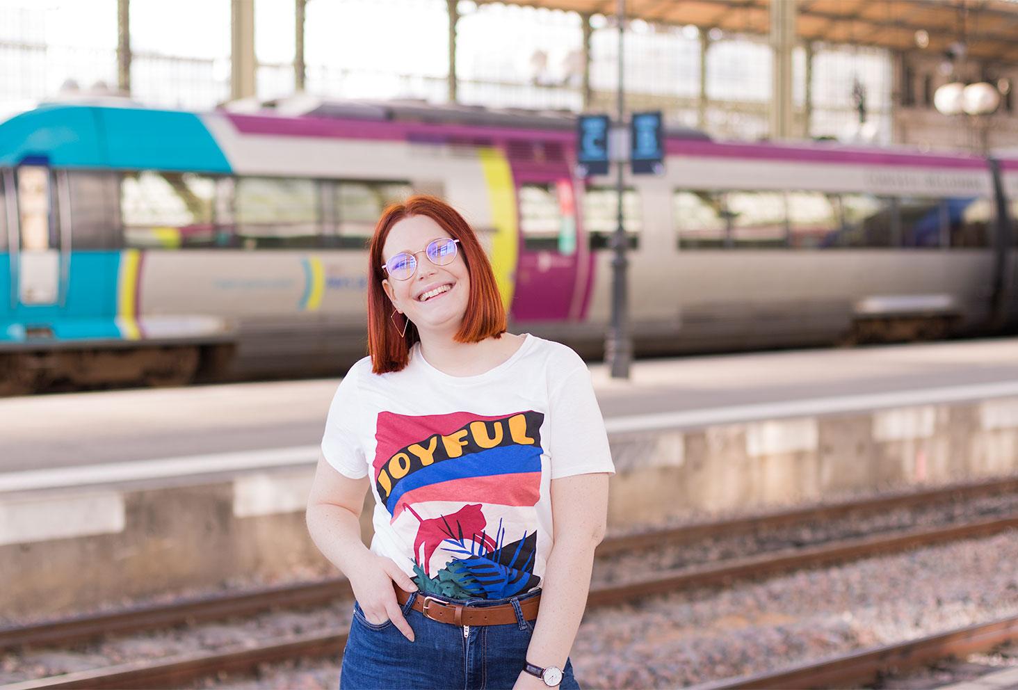 En t-shirt Joyful Kiabi devant le train à la gare, avec une main dans la poche et le sourire