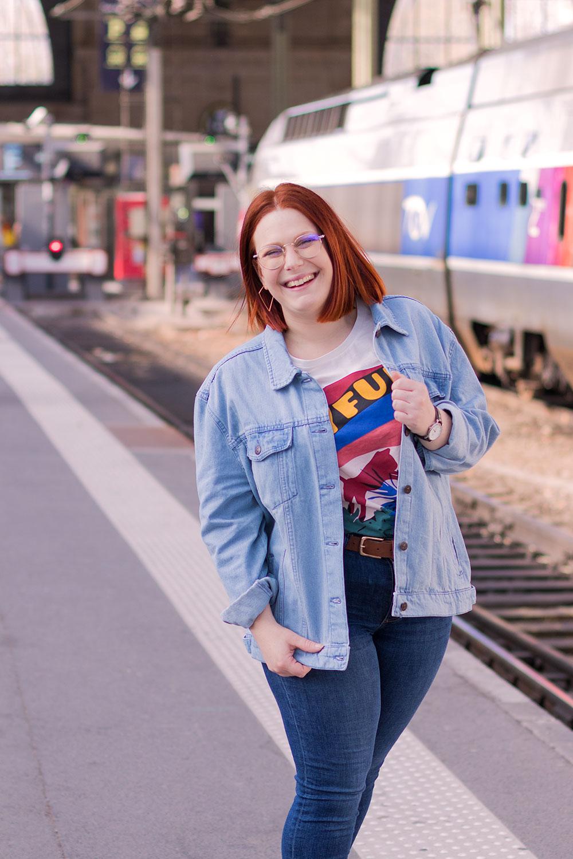 Devant les railles du train de la gare de Tours en t-shirt et veste en jean loose avec le sourire