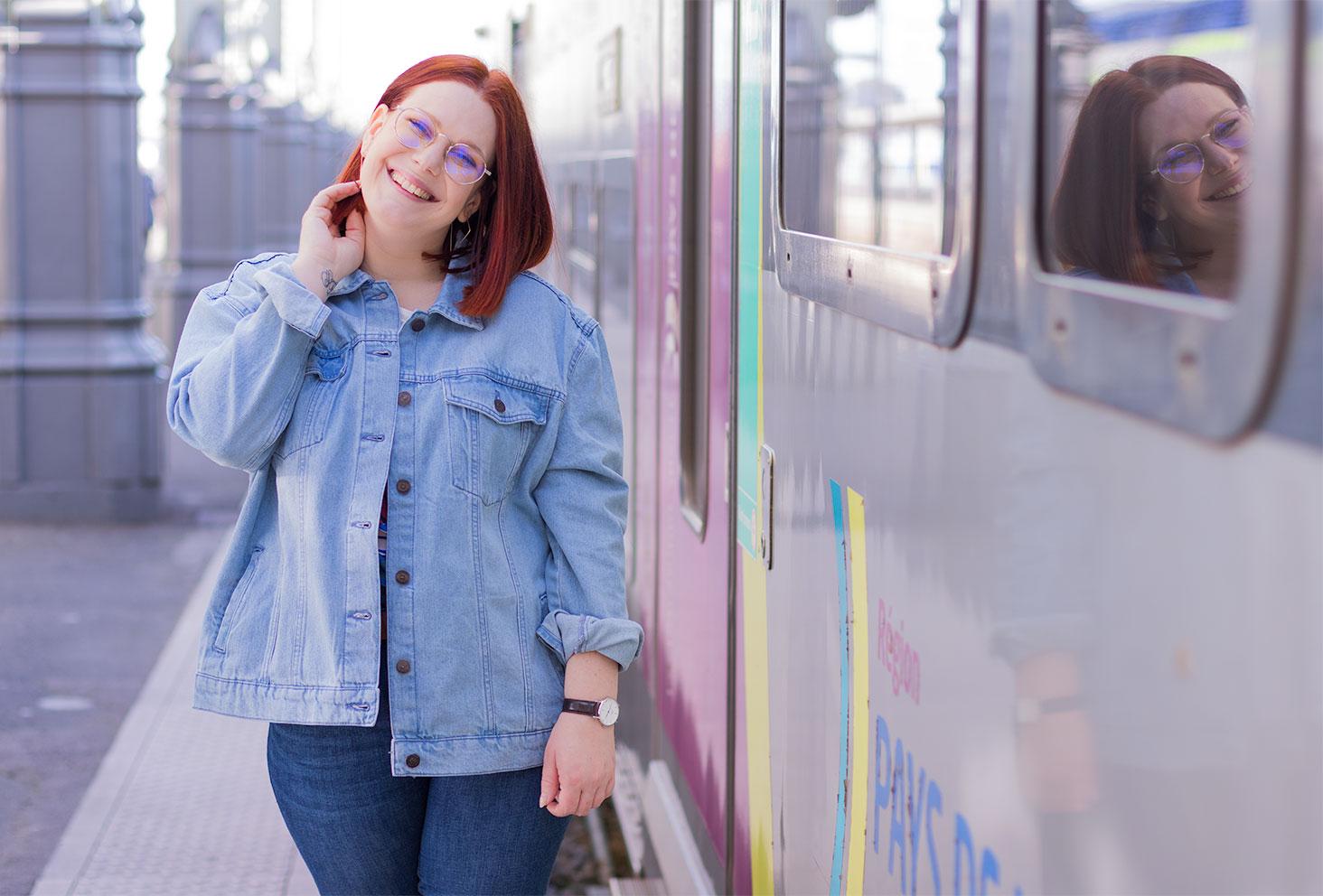 Zoom sur la veste en jean bleue claire loose Kiabi, portée avec le sourire à côté d'un train prêt à démarrer