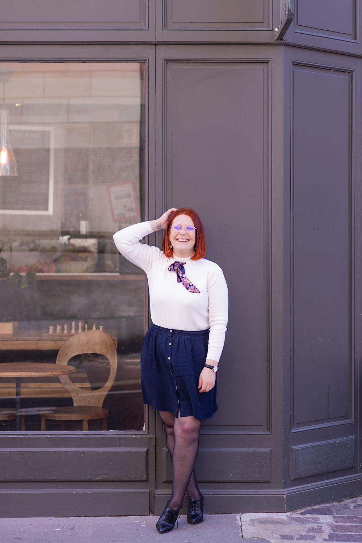 Devant la vitrine d'un café, la main sur la tête avec le sourire, en pull blanc SheIn et jupe fluide bleue marine