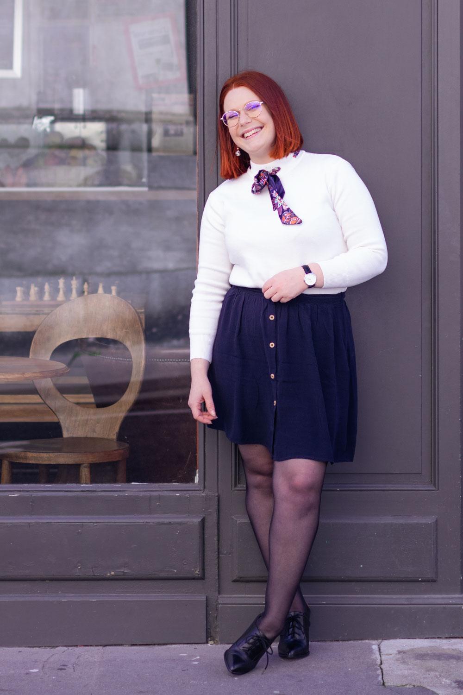 Avec le sourire appuyé le dos le long de la vitrine d'un café, en jupe bleue avec un pull blanc