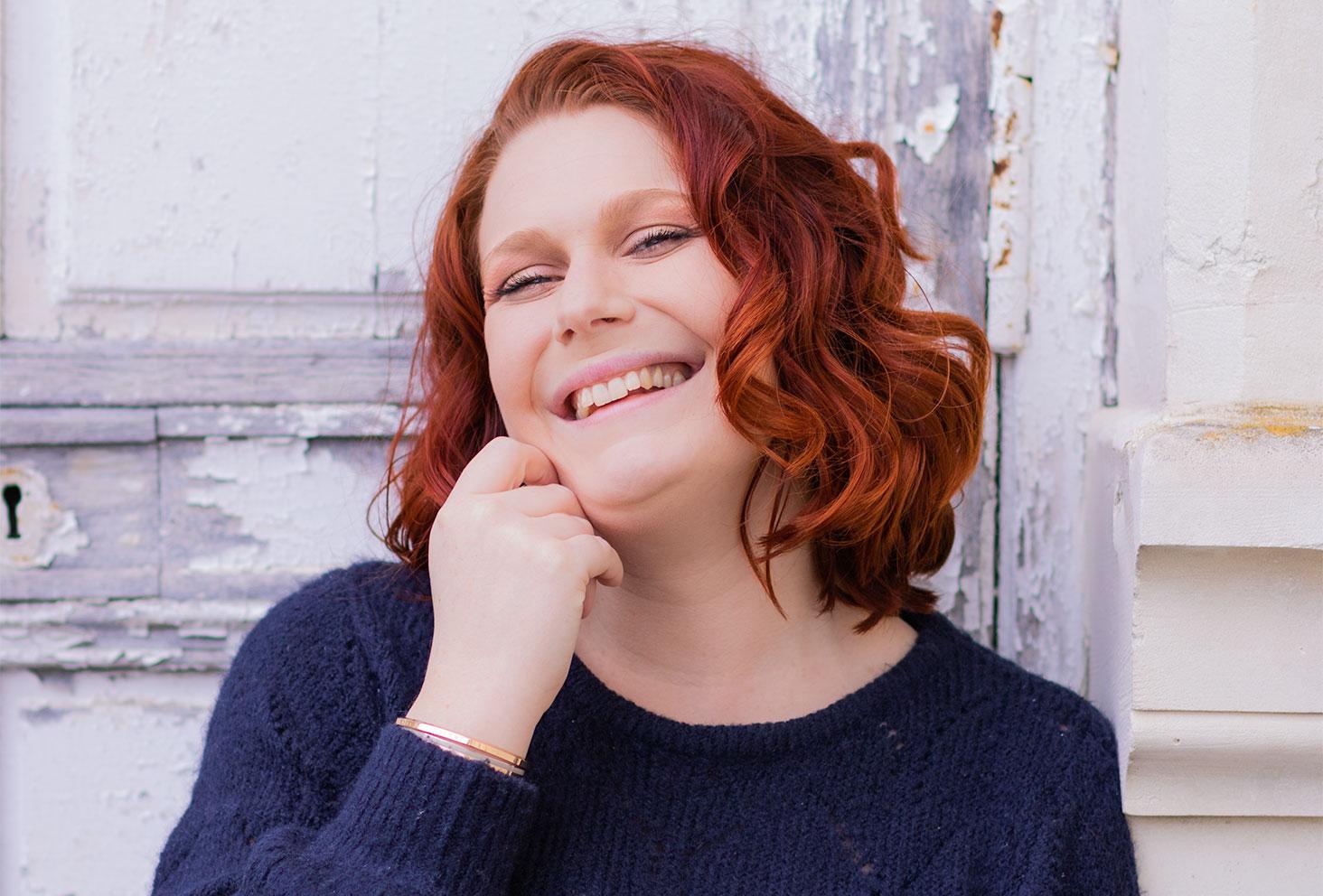 Zoom sur les cheveux roux bouclés devant une porte bleue vieillie