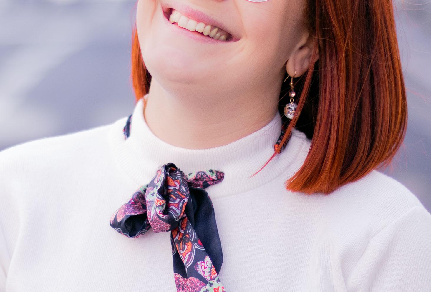 Zoom sur le col du pull blanc Shein, avec un foulard noué dans le pull