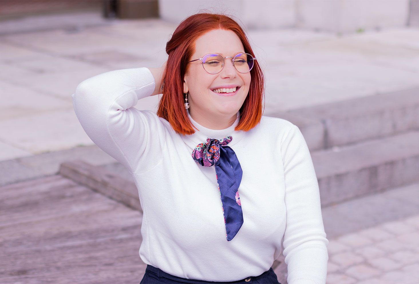 De profil, assise devant des escaliers en pierre, la main dans les cheveux avec le sourire, en pull blanc à col noué en foulard